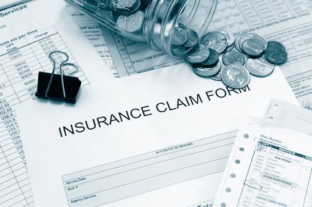 Diverse medische rekeningen en een claimformulier met munten Stockfoto