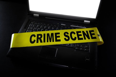 laptop with crime scene tape across it photo