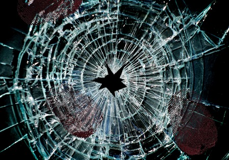shattered glass: Broken window with a hole in the middle and finger prints