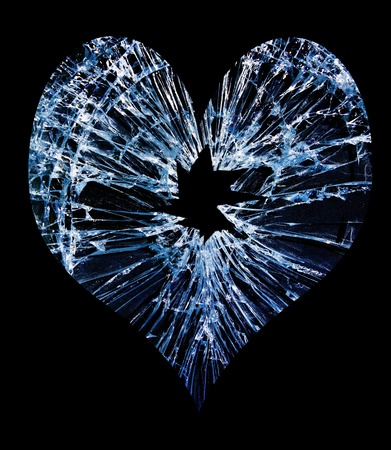 heart shaped shattered glass with a hole in the middle                                Stock Photo