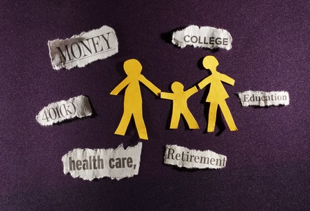 Family of three paper cutout figures and financial related news items                                photo