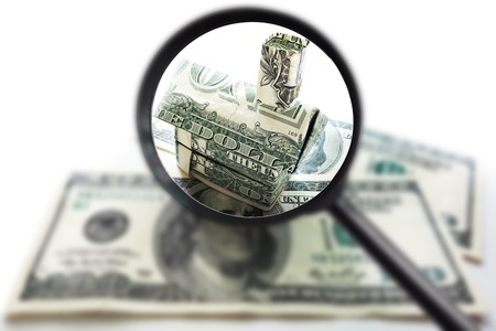 Origami dollar house on cash wth magnifying glass, over white                                photo