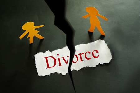 torn piece of paper with divorce text and paper couple figures photo