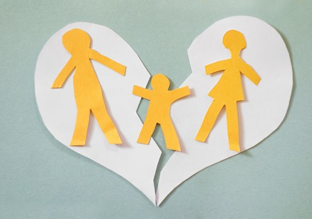 in custody: Paper cutout family split apart on a paper heart - divorce concept