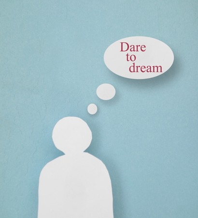 Paper person cutout with Dare To Dream thought bubbles                               Stock Photo