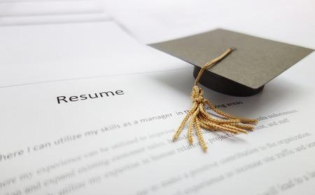 Small graduation cap on a resume - recent college graduate concept