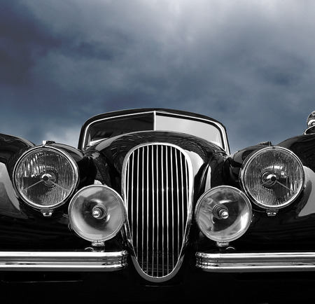 Vintage car front view with dark clouds Imagens