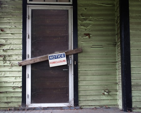 condemned: An old vacant house with Foreclosure sign on door