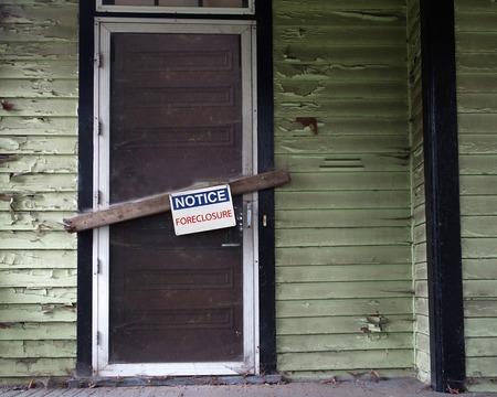 vago: Uma casa vazia velha com sinal Foreclosure na porta