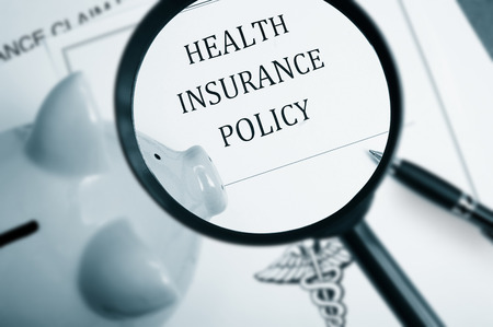 financial insurance: Magnifying glass over health insurance policy and piggy bank