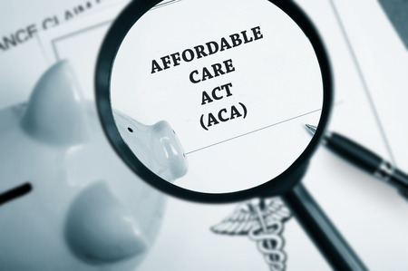 Magnifying glass over Affordable Care Act policy and piggy bank Standard-Bild