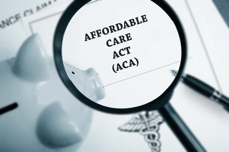 Vergrootglas over Affordable Care Act beleid en spaarvarken Stockfoto