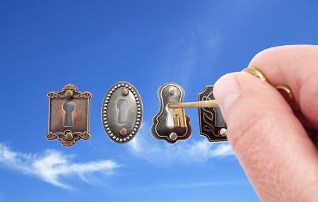 Vintage locks with hand, key and sky