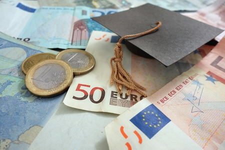 euro bill: Euro notes and coins with mini graduation cap