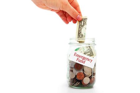 white fund: hand putting a money into Emergency Fund jar - Rainy Day fund concept