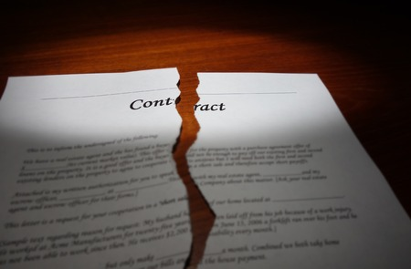 broken contract: Torn legal contract on a desk