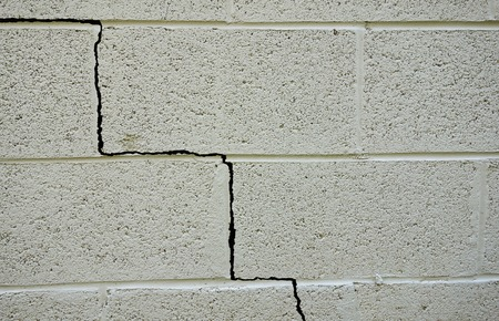cracked cement: Crack in a cinder block building foundation Stock Photo