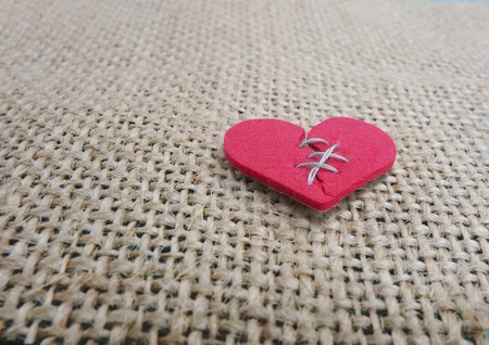 heart background: Red stitched broken heart on textured background