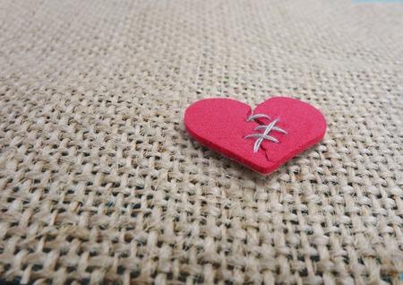 corazon roto: Rojo cosido coraz�n roto sobre fondo de textura Foto de archivo