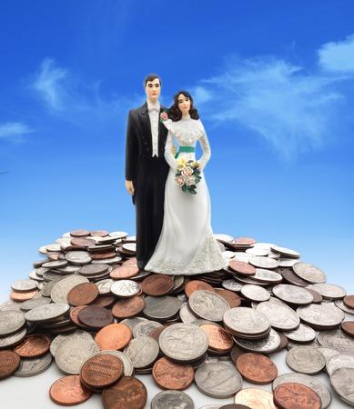 plastic money: Plastic wedding couple on coins - money concept Stock Photo