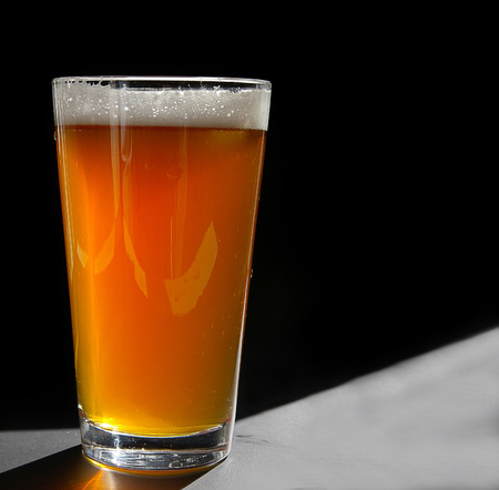 Pint glass of craft beer, backlit on black