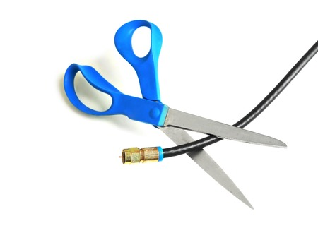 to cut: Scissors cutting through a coaxial cable - cut the cable tv concept