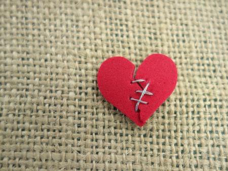 corazon roto: Corazón rojo roto cosido con hilo Foto de archivo