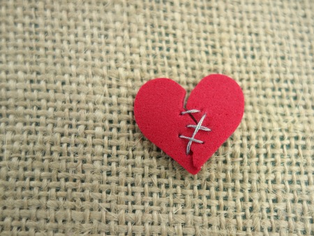 broken relationship: Red broken heart stitched with thread Stock Photo