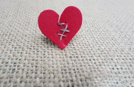 Broken red heart with threaded stitches