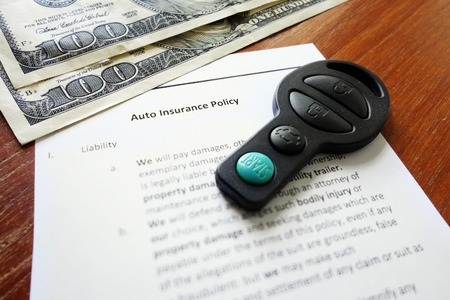 Car insurance policy with key fob and cash photo