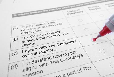 Close-up van een werknemer enquête met rode pen