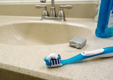 enjuague bucal: Cepillo de dientes, hilo dental y enjuague bucal en el lavabo del ba�o