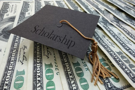 scholarship: Mini graduation mortar board with Scholarship text, on money Stock Photo