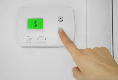 bill: Person adjusting a wall thermostat with dollar sign symbol on the display