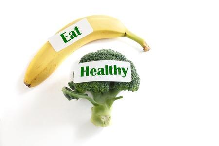 comer sano: Br�coli fresco y pl�tano con Coma etiquetas saludables, sobre fondo blanco