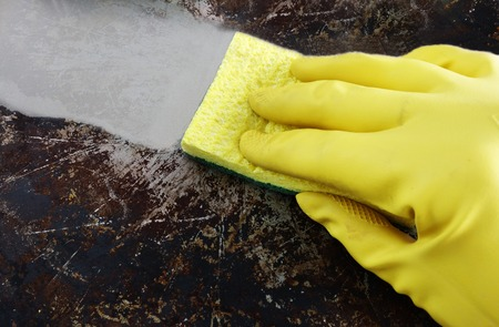 greasy: Cleaning a greasy pan with yellow latex gloves