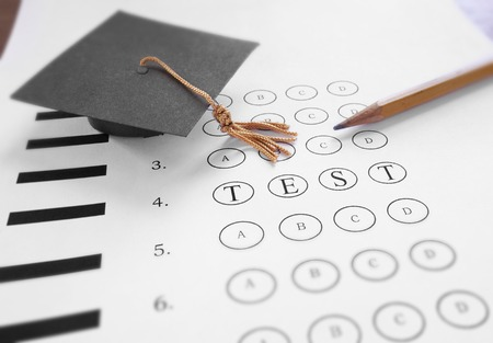multiple choice: Mini mortar board graduation cap and Test text on multiple choice exam