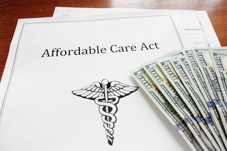 Affordable Care Act insurance papers with cash Archivio Fotografico