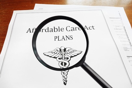 affordable: Affordable Care Act Plans document and magnifying glass