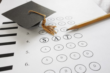 test paper: SAT test with pencil and mortar board graduation cap