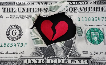 Torn dollar with broken red heart in the center photo