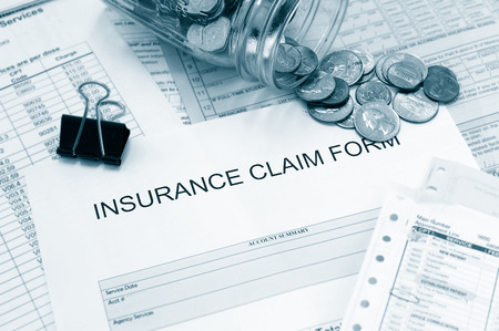 premiums: Patient medical bills and claim form with coin jar