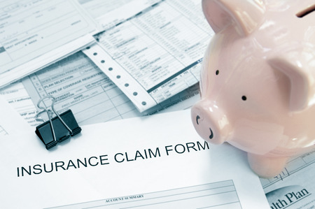medical bills: Patient medical bills and insurance claim form, with piggy bank