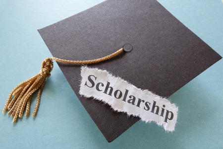 scholarship: Scholarship paper note on a graduation cap