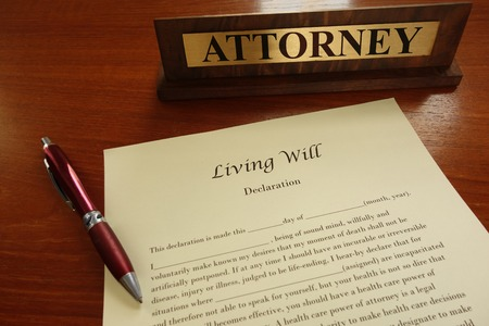 A living will document with pen and attorney name plate