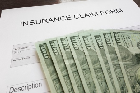 Insurance claim form and assorted money Standard-Bild