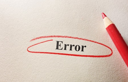 Error circled in red pencil on textured paper photo