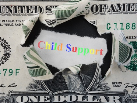 Hole ripped in a dollar bill with colorful Child Support text
