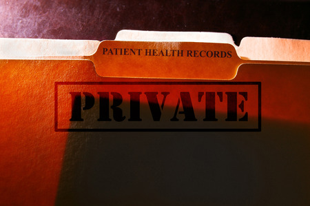 private information: File folders with Patient Health Records label and Private stamp Stock Photo