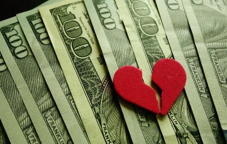 Broken red heart on assorted cash